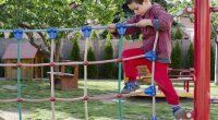 Child palying at children playground, climbing on  rope ladder obstacle course equipment.