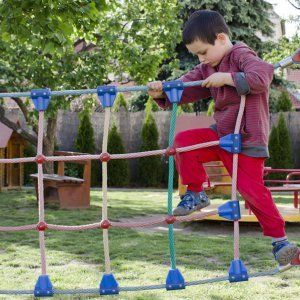 : Child palying at children playground, climbing on  rope ladder obstacle course equipment.